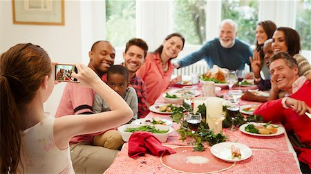 6113-08805635 © Masterfile Royalty-Free Model Release: Yes Property Release: Yes Girl with camera phone photographing multi-ethnic family at Christmas dinner table
