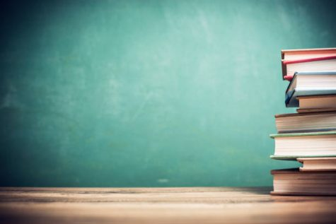 Back to school.  Textbooks stacked on wooden school desk in front of green chalkboard.  Classroom setting.